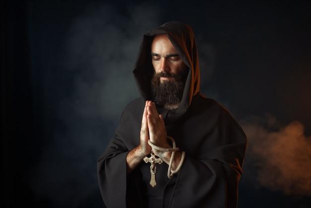 Средневековый монах в черной мантии с капюшоном молится с закрытыми глазами, секретный ритуал. таинственный монах в темном плаще. тайна и духовность