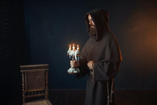 Средневековый монах в халате держит в руках подсвечник
