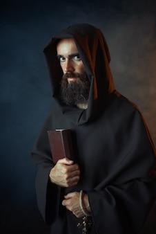 Средневековый монах в мантии держит книгу заклинаний в руках