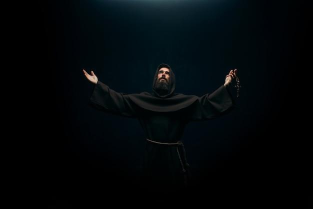 Средневековый монах молится святому богу, религии. таинственный монах в темном плаще, тайна и духовность