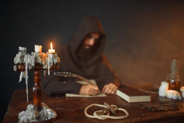 Средневековый монах сидит за столом и пишет, вид сверху