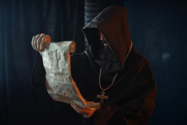 Средневековый монах со злым лицом читает молитву