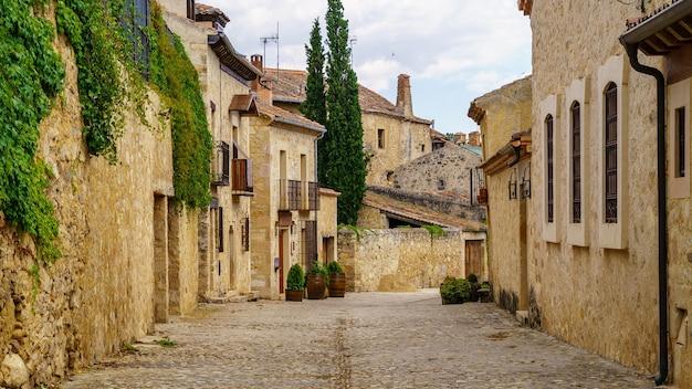 石造りの家、古いドアや窓、石畳の通り、絵のように美しい雰囲気のある中世の旧市街。ペドラサ、セゴビア、スペイン、ヨーロッパ。