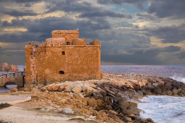 Средневековый замок пафоса на берегу моря на закате
