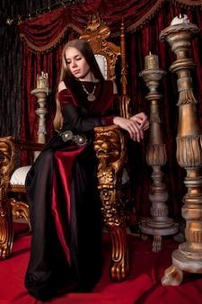 Средневековая королева в историческом наряде на золотом троне в замке. портрет молодой женщины в платье старого стиля на античном троне в приемной крепости. концепция тематических костюмированных мероприятий