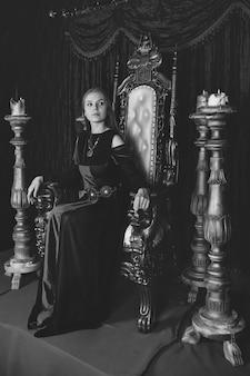 Средневековая королева в историческом наряде на золотом троне в замке. портрет молодой женщины в старинном платье на античном троне в приемной крепости. концепция тематических костюмированных мероприятий