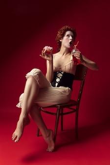 Средневековая рыжая молодая женщина в образе герцогини в черном корсете и ночной рубашке, сидящая на стуле на красном пространстве с напитком и пончиком