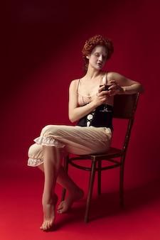 Средневековая рыжая молодая женщина в образе герцогини в черном корсете и ночной одежде, сидящая на стуле на красном пространстве с бокалом вина