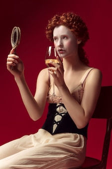Средневековая рыжая молодая женщина в образе герцогини в черном корсете и ночном белье сидит на красном пространстве с зеркалом и бокалом вина