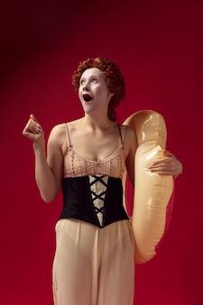 Средневековая рыжая молодая женщина в образе герцогини в черном корсете и ночной рубашке, стоящая на красном