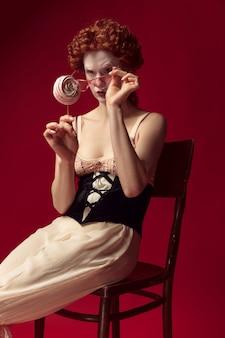 Средневековая рыжая молодая женщина в образе герцогини в черном корсете, солнечных очках и ночной одежде, сидящая на стуле на красном пространстве с конфетой