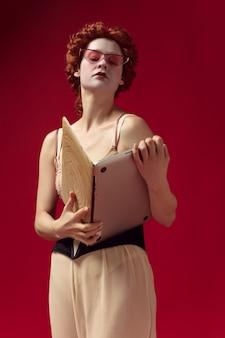 黒いコルセット、サングラス、寝間着を着た公爵夫人としての中世の赤毛の若い女性が、ノートパソコンを本として赤い壁に立っています。時代、現代性、ルネッサンスの比較の概念。