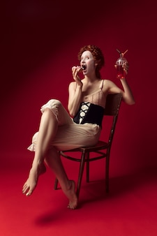 Medieval redhead young woman as a duchess in black corset and night clothes sitting on a chair on red space with a drink and donut
