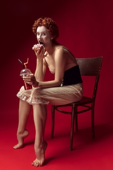 Redhead medievale giovane donna come una duchessa in corsetto nero e abiti da notte seduta su una sedia su uno spazio rosso con un drink e ciambella