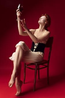 Redhead medievale giovane donna come una duchessa in corsetto nero e abiti da notte seduta su una sedia su uno spazio rosso con un bicchiere di vino