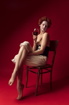 Medieval redhead young woman as a duchess in black corset and night clothes sitting on a chair on red space with a glass of wine