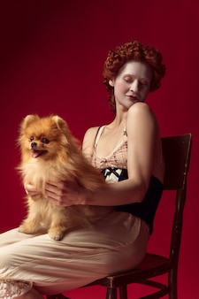 Medieval redhead young woman as a duchess in black corset and night clothes sitting on a chair on red space with a little puppy or dog