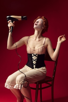 Medieval redhead young woman as a duchess in black corset and night clothes sitting on the chair on red wall. doing her hair with dryer. concept of comparison of eras, modernity and renaissance.