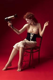 Redhead medievale giovane donna come una duchessa in corsetto nero e abiti da notte seduta sulla sedia sul muro rosso. facendosi i capelli con l'asciugatrice. concetto di confronto tra epoche, modernità e rinascita.