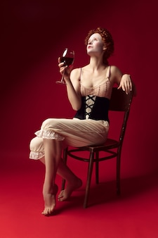 Medieval redhead young woman as a duchess in black corset and night clothes sitting on the chair on red wall. drinking red wine. concept of comparison of eras, modernity and renaissance.