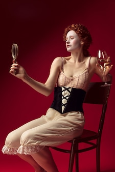 Medieval redhead young woman as a duchess in black corset and night clothes sitting on red wall with a mirror and a glass of wine. concept of comparison of eras, modernity and renaissance.