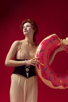 Redhead medievale giovane donna come una duchessa in corsetto nero e abiti da notte in piedi su uno spazio rosso con un cerchio di nuotata come una ciambella