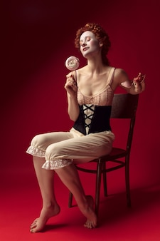 Medieval redhead young woman as a duchess in black corset, sunglasses and night clothes sitting on a chair on red space with a candy
