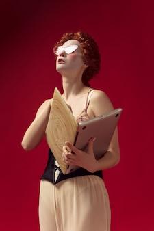 Redhead medievale giovane donna come una duchessa in corsetto nero, occhiali da sole e abiti da notte in piedi su uno spazio rosso con un laptop come un libro