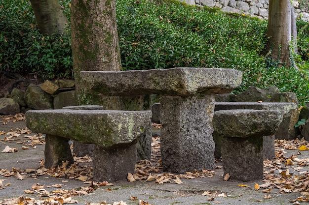 Средневековый каменный стол и скамейки в парке порту, португалия