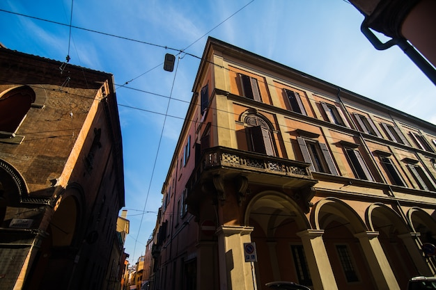 Medieval street portico with bright colored houses in the old town in the sunny day, bologna, emilia-romagna, italy