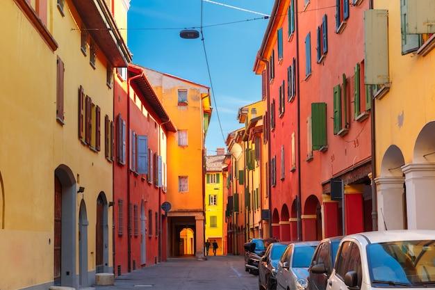 Средневековый уличный портик с цветными домами в старом городе болоньи, италия