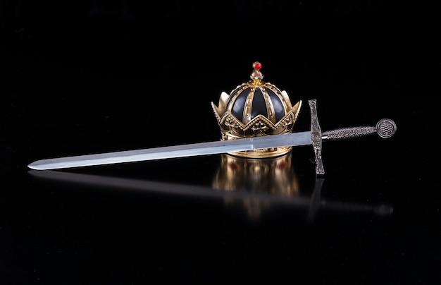 Средневековый меч и корона на черном фоне изолированных