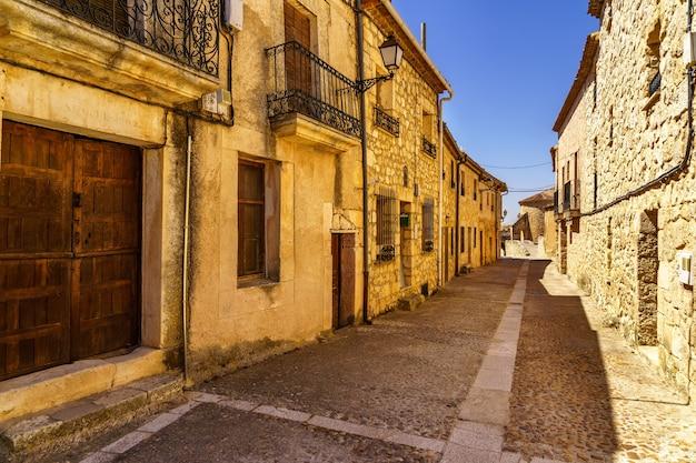 석조 주택, 조약돌 거리, 오래된 문과 창문, 아치와 벽이있는 중세 마을입니다. maderuelo segovia 스페인.
