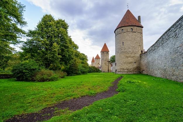 Средневековая стена с высокими каменными башнями и красными крышами в таллинне, эстония.