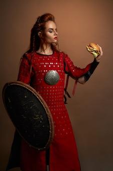 ハンバーガーを保持している中世の戦士がポーズします。