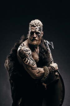 Medieval warrior viking with tattoo beard and braids in hair with axe and shield