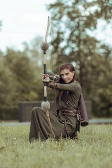 Средневековая женщина-воин с луком сидит на поляне и целится из лука, охотясь в зеленом лесу