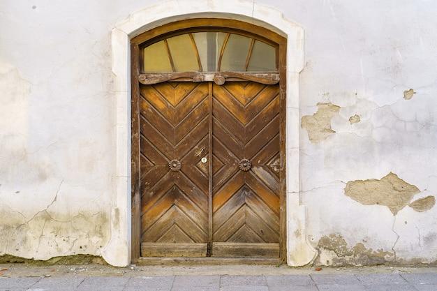 劣化した漆喰のファサードの中世の木製ドア。