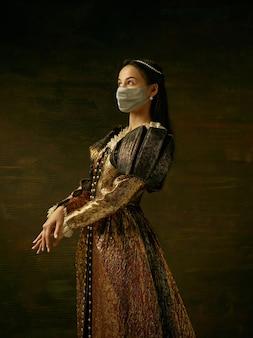 코로나바이러스에 대한 보호 마스크를 쓴 공작부인으로 중세 젊은 여성이 어두운 파란색 배경에 퍼졌습니다. 시대, 의료, 의학 및 전염병 예방의 비교 개념.