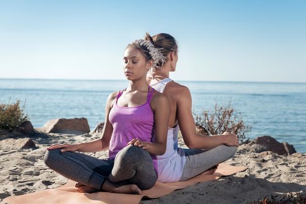 彼氏と瞑想する。川の近くで彼女のボーイフレンドと一緒に瞑想するドレッドヘアを持つスリムな美しい女性