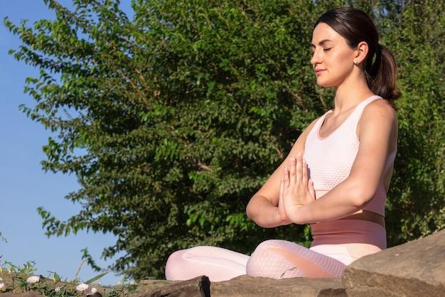 Медитирует на природе. девушка занимается йогой на улице, в розовом спортивном костюме выполняет различные упражнения и позы йоги