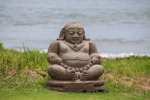 Meditating buddha statue on tropical beach in bali, indonesia