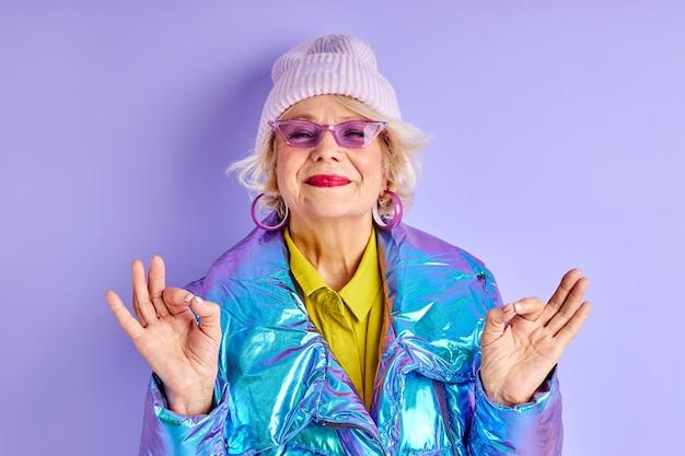 派手な服を着て瞑想する女性、ヨガに熱心な楽観的な白人の成熟した女性、孤立した笑顔のカメラを見てください