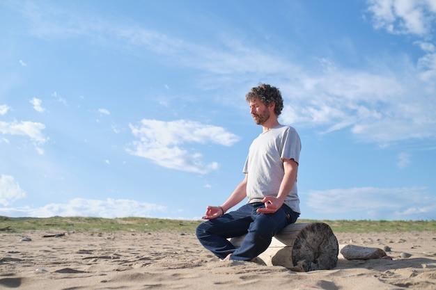 해변에 앉아 명상 남자