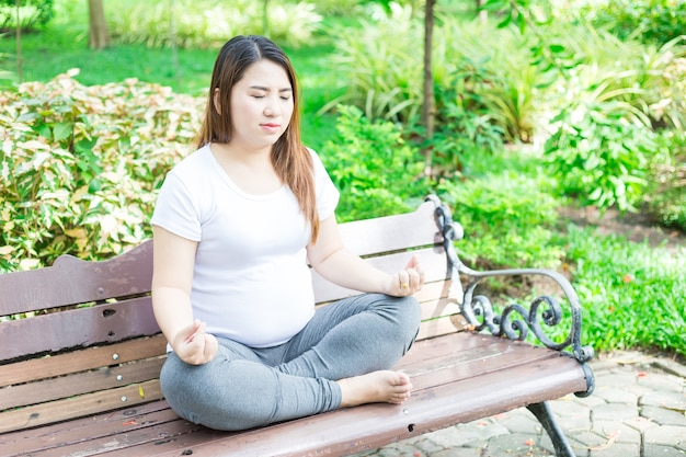 Размышление о материнстве. крупным планом молодая беременная женщина медитации, сидя на деревянном стуле