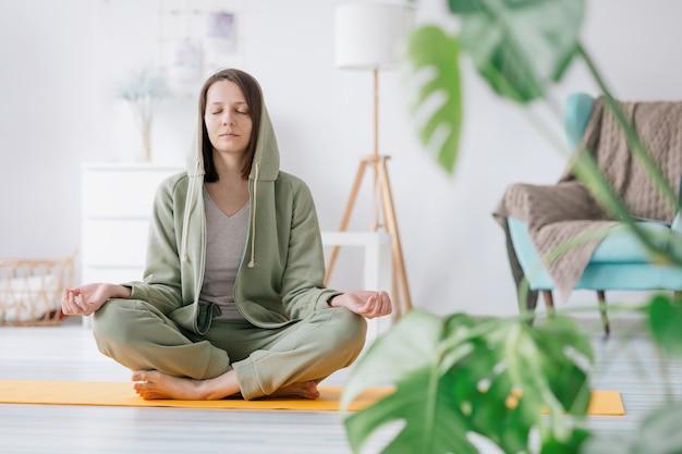 Медитация и йога дома красивая и молодая европейская женщина занимается йогой