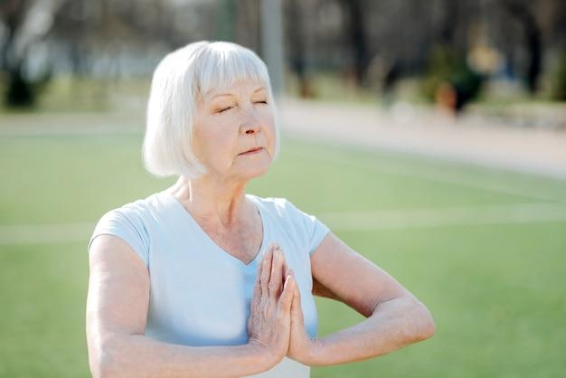 瞑想。野外で運動しながらヨガをしている集中老婆