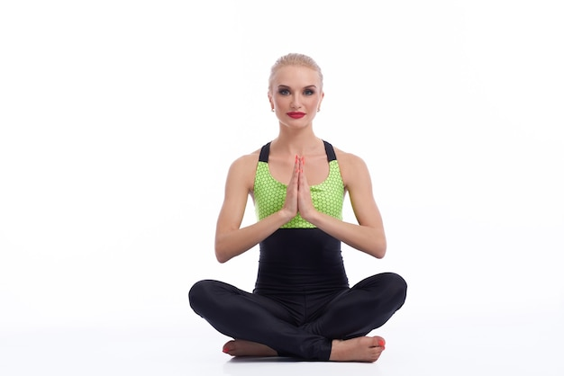 La meditazione è la chiave. ritratto in studio di una bellissima giovane donna seduta in lotus asana meditando mentre pratica yoga sorridendo felicemente isolato copyspace