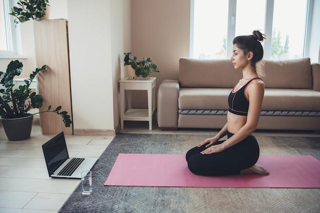 コンピューターと水とガラスを使用してスポーツウェアを身に着けているブルネットの女性の床での瞑想レッスン