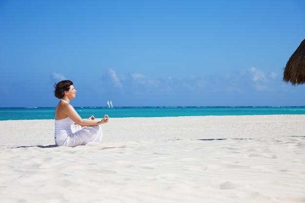 ビーチで蓮華座の幸せな女性の瞑想